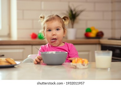 happy baby sitting at the table in the kitchen and eating with an appetite