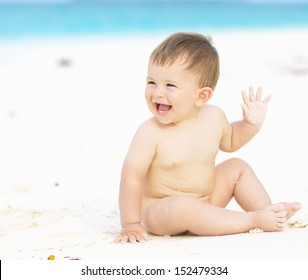 Happy baby smiling and waving hand, sitting on white sandy tropical beach