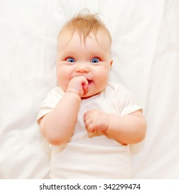 Happy baby sucking his finger on a white bed. Good morning!
