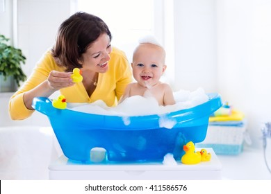Happy baby taking a bath playing with foam bubbles. Mother washing little boy. Young child in a bathtub. Smiling kids in bathroom with toy duck. Mom bathing infant. Parent and kid play with water.