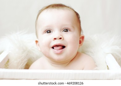 happy baby in white basket