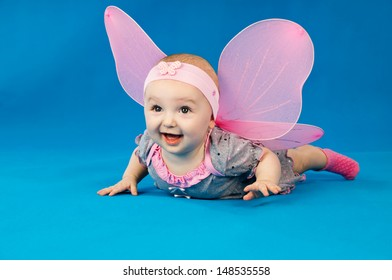 happy baby with wings on blue background