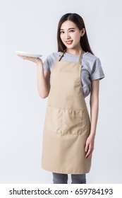 Happy baker chef in apron holding a plate