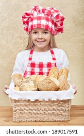 Happy baker holding a basket with fresh bakery products
