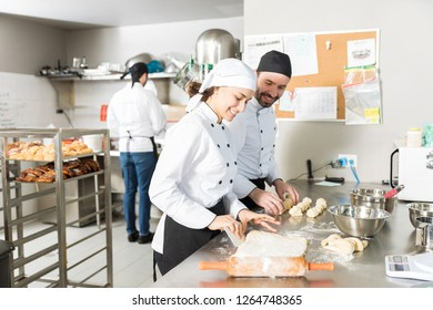 Happy bakers making dough for bread pastries in restaurant kitchen