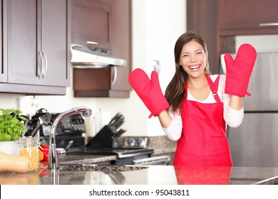 Happy baking cooking woman standing in her new kitchen smiling cheerful wearing apron and oven mitts ready to bake. Beautiful young mixed race Caucasian / Chinese woman at home.