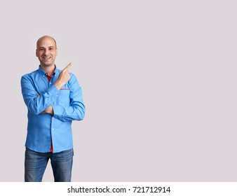 happy bald man pointing finger to copy space. Isolated on grey background