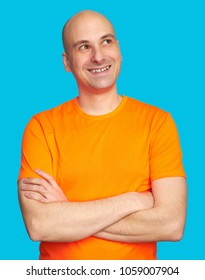 Happy bald man toothy smiling and looking up. Cheerful guy in bright orange shirt thinking. Isolated on blue background