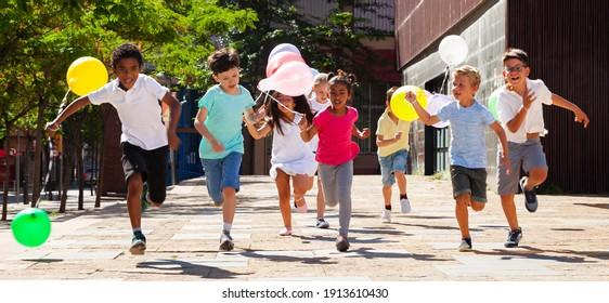 Glücklich mit Ballons laufen auf der Sommerstadtstraße. Hochwertiges Foto
