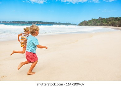 Happy barefoot kids have fun on beach walk. Run and jump by white sand along sea surf. Family travel lifestyle, outdoor sports activities and games. Summer vacation with children on tropical island