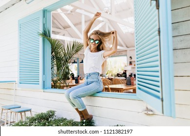 Happy barefooted woman in vintage jeans enjoying morning in summer. Glad fair-haired female model in casual t-shirt playing with her hair while sitting on window sill.