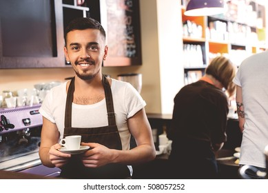 happy barista holding a mug while standing in the kitchen