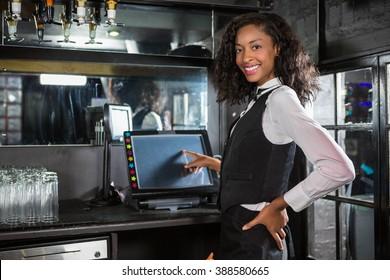 Happy barmaid preparing a bill in bar