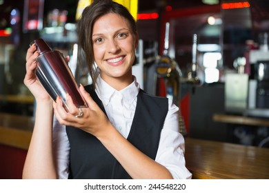 Happy barmaid smiling at camera making cocktail in a bar