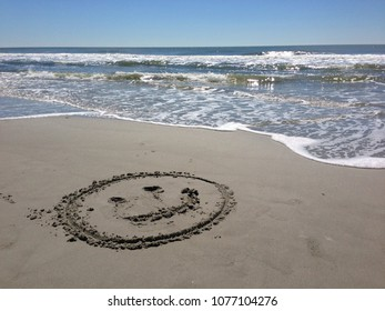 Happy to be at the beach! A smiling face is drawn in the sand along the surf.