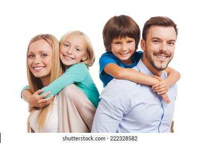 Happy to be a family. Happy family of four bonding to each other and smiling while standing against white background