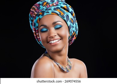 Happy to be herself. Happy young African woman wearing a headscarf and necklace and keeping eyes closed while standing against black background