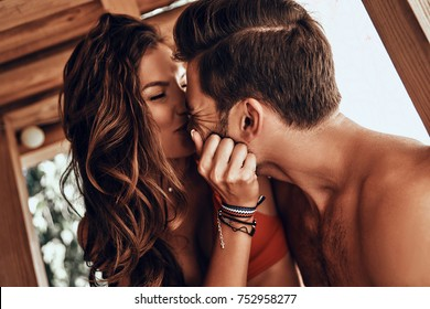 Happy to be in love. Beautiful young couple sitting face to face and smiling while resting in the beach hut