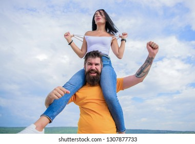 Happy to be in love. Happy couple in love on cloudy sky. Bearded man piggybacking his girlfriend just for fun. Hipster giving sexy woman a piggyback ride. Loving couple happy smile having fun.