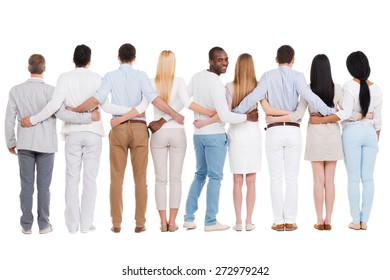 Happy to be in team. Full length rear view of group of diverse people bonding to each other and standing against white background while one African man looking over shoulder and smiling