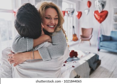 Happy to be together. Beautiful young couple embracing and smiling while spending time in the bedroom
