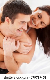 Happy to be together. Beautiful young loving couple having fun while sitting together in bed