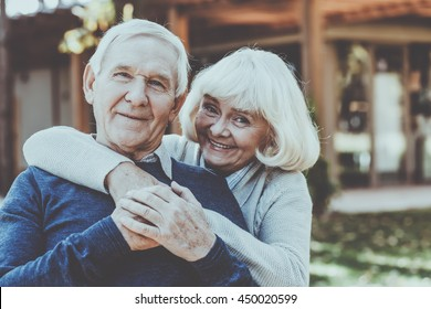 Happy to be together. Happy senior couple bonding to each other and smiling while standing outdoors and in front of their house