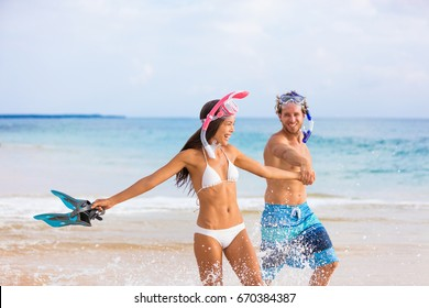 Happy beach couple having fun splashing water on snorkel swim. Young people laughing on summer travel vacation, bikini woman, snorkel man with diving mask and flippers running playful in waves.