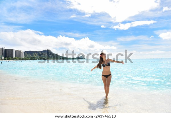 Happy beach woman in bikini joyful and free on Waikiki, Oahu, Hawaii, USA. Girl on travel vacation holidays having fun on Hawaiian Waikiki beach with Diamond Head mountain. Asian Caucasian model.