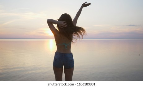 Happy beach woman waving hands hello saying on Hawaii. Portrait of multiracial Asian Caucasian woman on beach. Hello summer concept. Slow motion