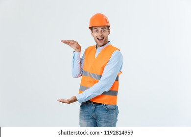 Happy beard engineer holding hand on side and explaining something, guy wearing caro shirt and jeans with yellow vest and orange helmet, isolated on white background