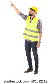 Happy beard engineer smiling and pointing to something, guy wearing caro shirt and jeans with yellow vest and helmet, isolated on white background