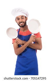 Happy beard young chef smiling and holding two pans, guy wearing a blue chef uniform and chef hat, isolated on white background