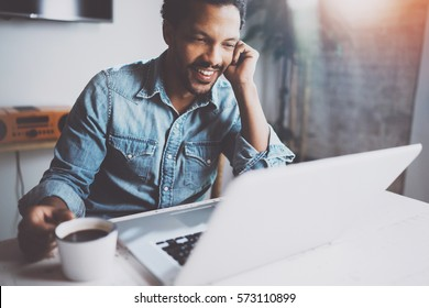 Happy bearded African man making video conversation via modern laptop with partners while holding white cup black coffee at home.Concept of young business people.Blurred background,flares effect