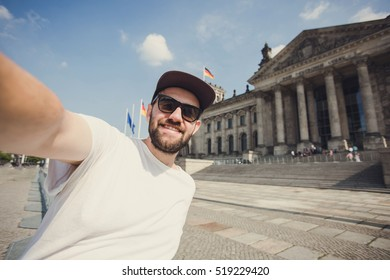 Happy bearded guy taking selfie near Reichstag in Berlin. Funny hipster student taking picture for travel blog in Germany.