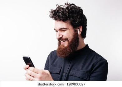 Happy bearded guy is typing sms on his smarphone sitting over white background
