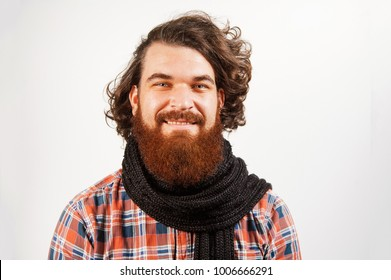Happy bearded hipster man with curly hair looking confident at the camera.