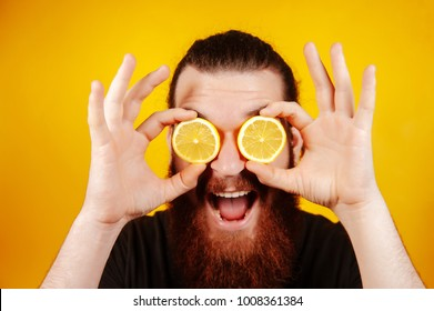 Happy bearded hipster man with sliced lemon on eyes over orange background. Man with long beard hold lemon.  Fruit and healthy organic food. Citrus vitamin.