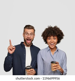 Happy bearded hipster points with index finger upwards, stands near his dark skinned girlfriend, spend free time together, drink coffee, isolated over white background. Interracial friendship