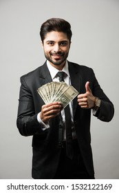 Happy bearded Indian businessman holding fan in hand, Indian Rupee currency bills of 500 , standing isolated over white background