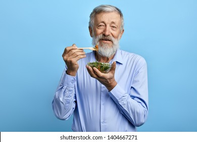 happy bearded man in blue shirt eating salad,health care concept. positive old man holding a bowl with salad and fork , healthy food, man leads healthy lifestyle , diet