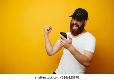 Happy bearded man celebrate success and looking at phone