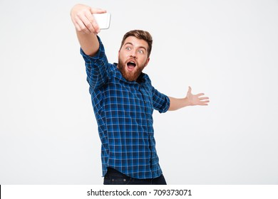 Happy bearded man in checkered shirt making selfie on his smartphone an showing something behind himself over gray background