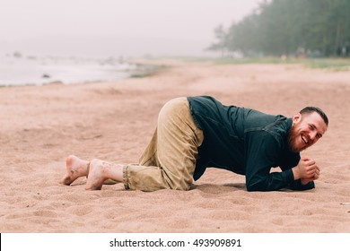 Happy bearded man crawling on all fours on the beach. bearded hipster on the beach