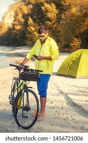Happy bearded man cyclist rides along the sandy beach on a mountain bike. Adventure travel.