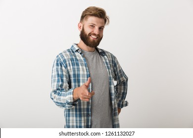 Happy bearded man dressed in plaid shirt standing isolated over white background, pointing at camera