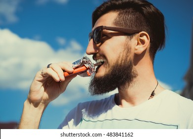 Happy bearded man eats chocolate. The bearded man smiling and posing with chocolate in hand. portrait outdoor close up