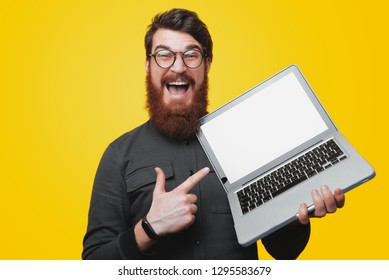 Happy bearded man in glasses holding and pointintg at laptop while looking at camera