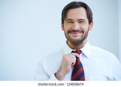 Happy bearded man grinning at the camera as he stands straightening his tie