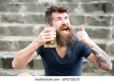 Happy bearded man having a drink after long day in office. Cheerful tipsy man holding beer mug while showing thumb up gesture, relax after work and weekend concept
